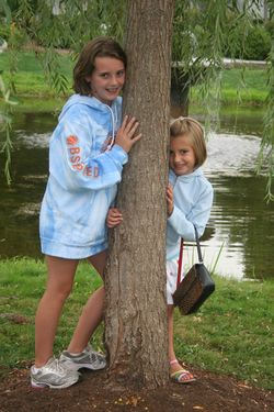 kids leaning on a tree